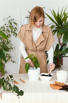 Giardinaggio della donna del colpo medio all'interno