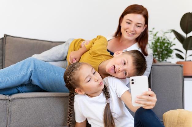 Donna e bambini del tiro medio che prendono selfie