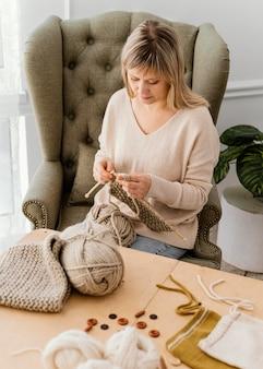 Donna del colpo medio che lavora a maglia sulla poltrona