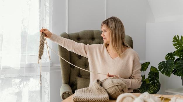 Donna del colpo medio che esamina articolo lavorato a maglia