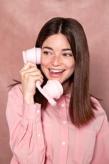 Donna del colpo medio che posa con il telefono