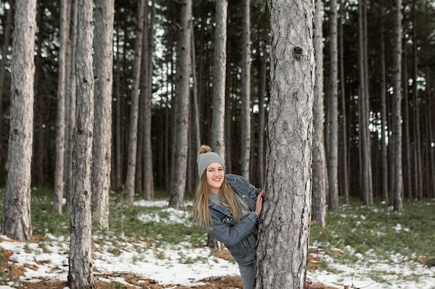Donna del colpo medio che posa con l'albero