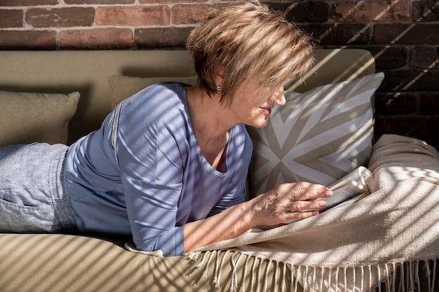 Donna del colpo medio che legge sul divano