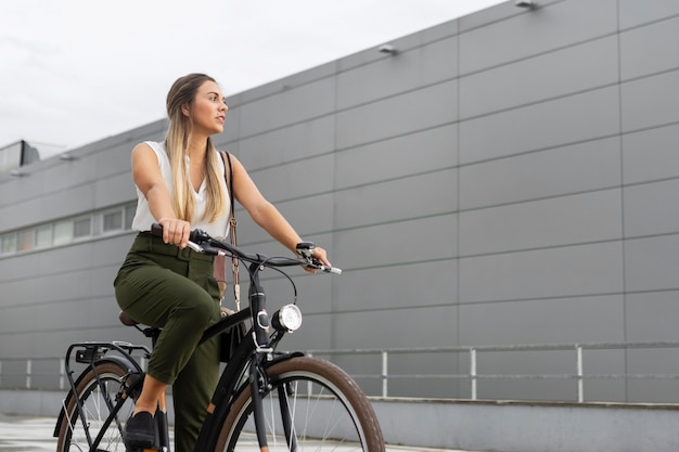 Donna del colpo medio che guida la sua bici