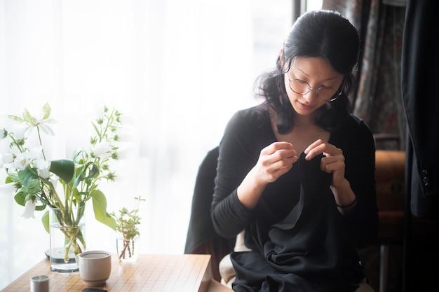 Colpo medio donna che cuce manualmente