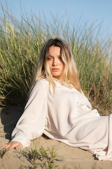 Donna del colpo medio che si siede sulla spiaggia