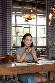 Colpo medio donna seduta a tavola con caffè with