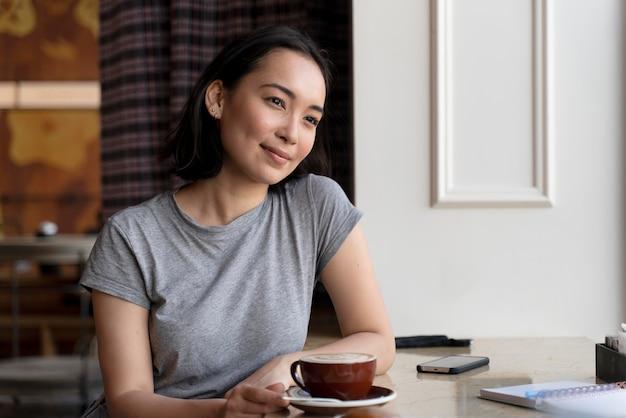 Donna del colpo medio che si siede con il caffè