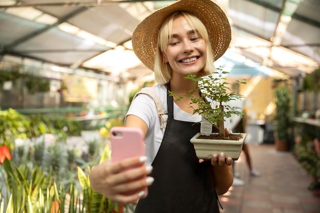Donna del colpo medio che prende selfie con la pianta