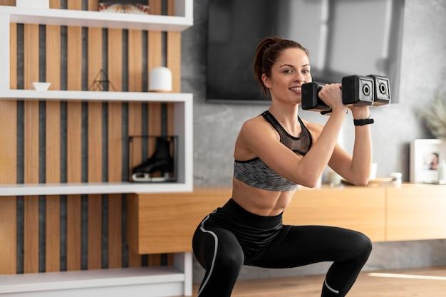 Donna di tiro medio allenamento con manubri