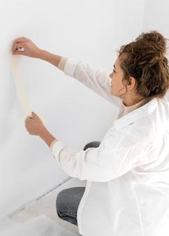 Donna del colpo medio usando del nastro adesivo
