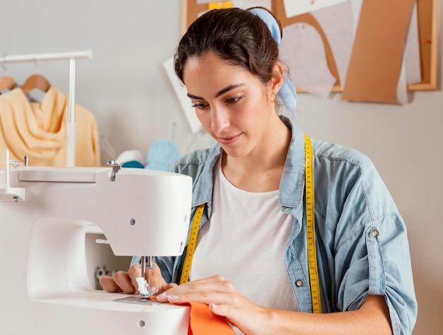 Donna del colpo medio usando la macchina da cucire