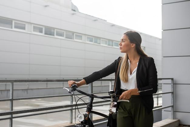 Donna del colpo medio con la bici che osserva via