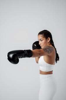 Donna del tiro medio con guantoni da boxe