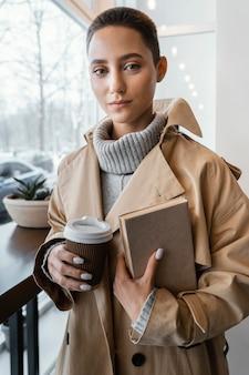 Donna del colpo medio con tazza e libro