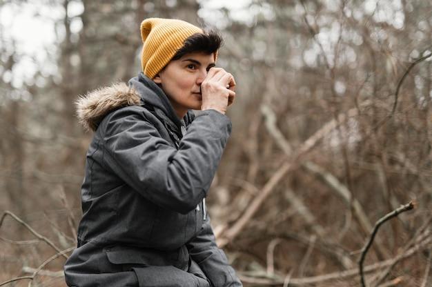 Donna del colpo medio con bevanda nella foresta