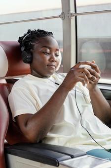 Donna del colpo medio con le cuffie in autobus