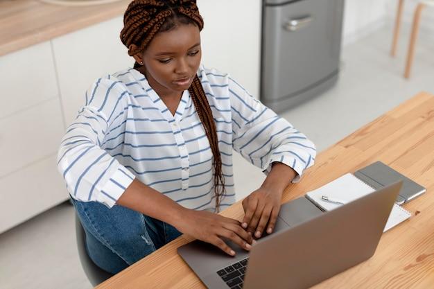 Donna a tiro medio con laptop in casa