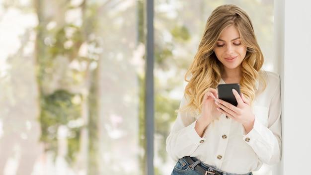 Colpo medio donna con telefono
