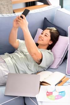 Donna del colpo medio con lo smartphone