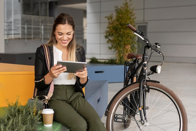 Donna di colpo medio con tablet e bici