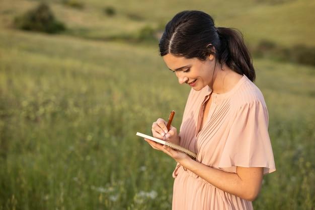 Scrittura della donna del colpo medio sul taccuino