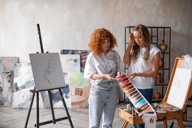 Donne a tiro medio che scelgono il colore della vernice