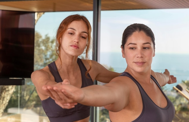 Donne del colpo medio che fanno yoga insieme