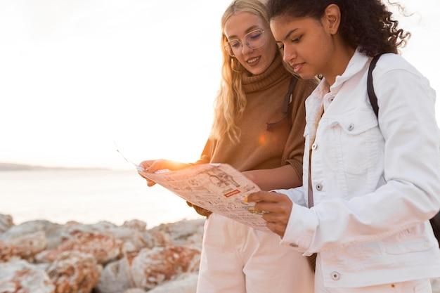 Donne del colpo medio che esaminano la mappa