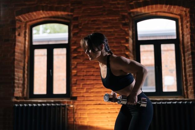 Colpo medio di giovane donna atletica con un bel corpo forte che indossa abbigliamento sportivo che si esercita con manubri. allenamento femminile caucasico di forma fisica fuori che si esercita nella palestra scura.