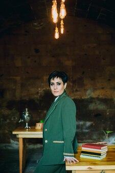 Un colpo medio di giovane donna che si appoggia sul tavolo in legno con libri che guarda attentamente la fotocamera in caffè retrò con oggetti vintage