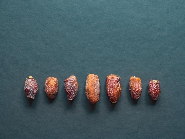 Le date di medjool al-madina sono disposte su un tavolo scuro.