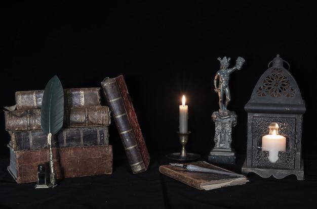 Statua di medusa accanto a libri antichi e lume di candela