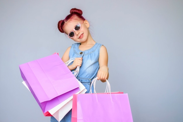 Incontra gli sconti. la piccola neonata felice sorride con i sacchetti della spesa di carta.