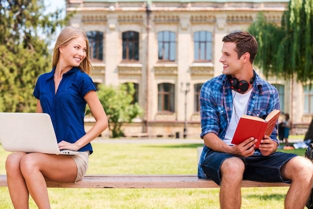 Incontrarsi per la prima volta. bel giovane seduto sulla panchina e leggendo un libro mentre una bella donna seduta vicino a lui e usando il computer