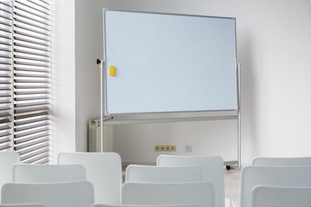 Sala riunioni con un grande consiglio scolastico bianco e sedie bianche. bella camera spaziosa in un ufficio moderno e luminoso..