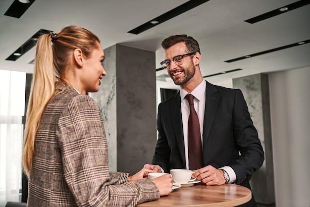 Incontro di due amici. uomo d'affari e donna nella hall dell'hotel a bere caffè. l'uomo tiene la mano della donna