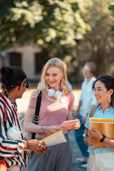 Incontro in cortile. due ragazze sorridenti che parlano con il loro allegro compagno di gruppo che torna a casa dopo l'università.