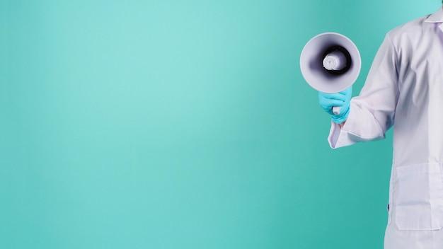 Megafono in mano. l'uomo indossa un camice da medico e un guanto medico blu su sfondo verde menta o tiffany blue. riprese in studio.