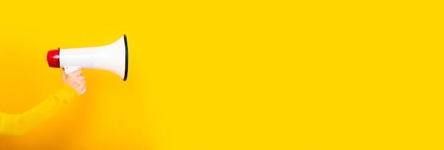 Megafono in mano su uno sfondo giallo