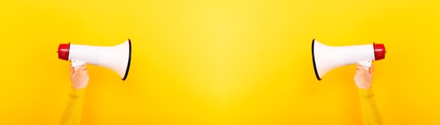 Megafoni nelle mani su uno sfondo giallo, concetto di attenzione