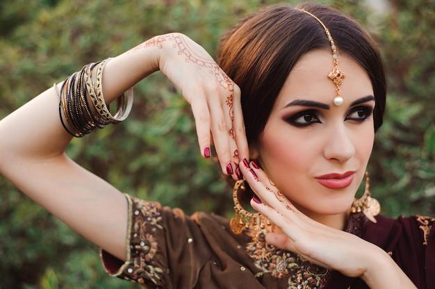 Mehendi sulle mani di ragazze, mani di donna con tatuaggio mehndi marrone. mani della ragazza indiana della sposa con i tatuaggi marroni dell'henné.