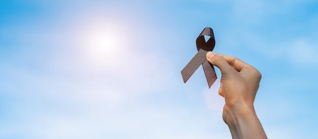 Melanoma e cancro della pelle, mese di sensibilizzazione sulle lesioni da vaccino e concetti di riposo in pace. uomo che tiene il nastro nero sullo sfondo del cielo