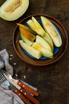 Melone melone fresco affettato in un piatto sul tavolo di legno spazio di copia