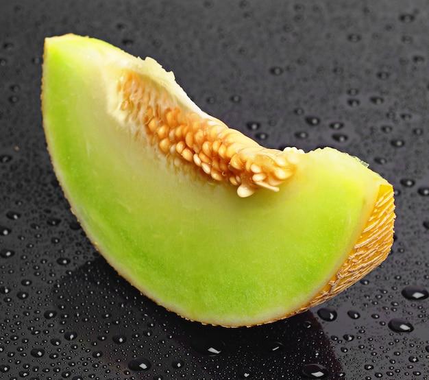Fette di melone su una tavola nera