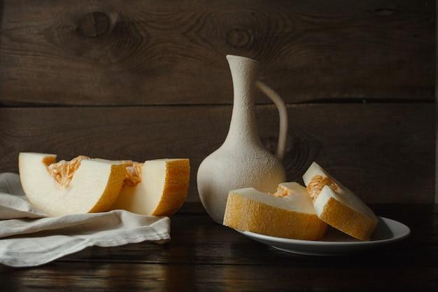 Fette di melone sul tavolo, brocca, fondo in legno