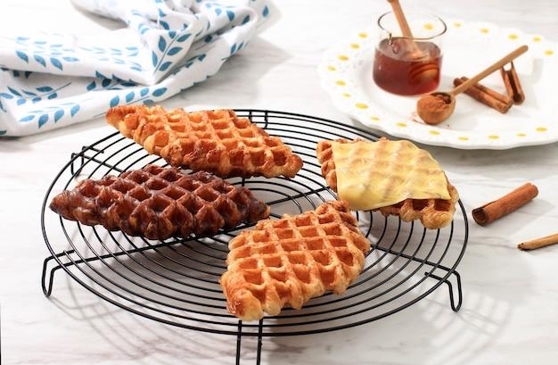 Croffe al formaggio fuso croisant waffle con vari condimenti, formaggio, cioccolato, zucchero e cannella. croffle è il cibo di strada virale dalla corea.