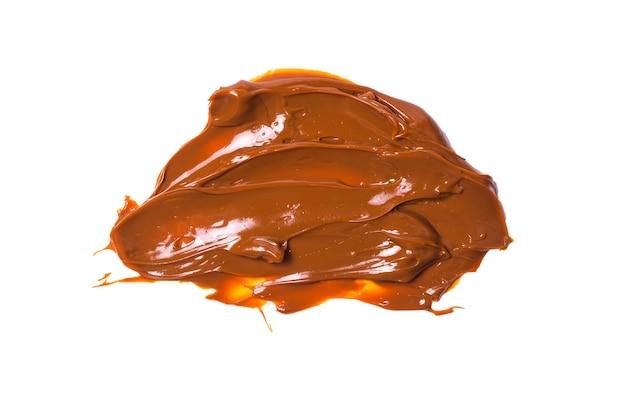 Spruzzi di caramello saporito fuso isolati su priorità bassa bianca.