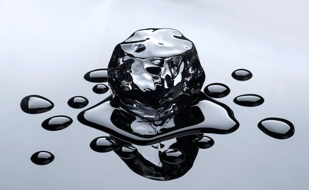 Cubetto di ghiaccio in fusione con gocce d'acqua su sfondo nero a specchio