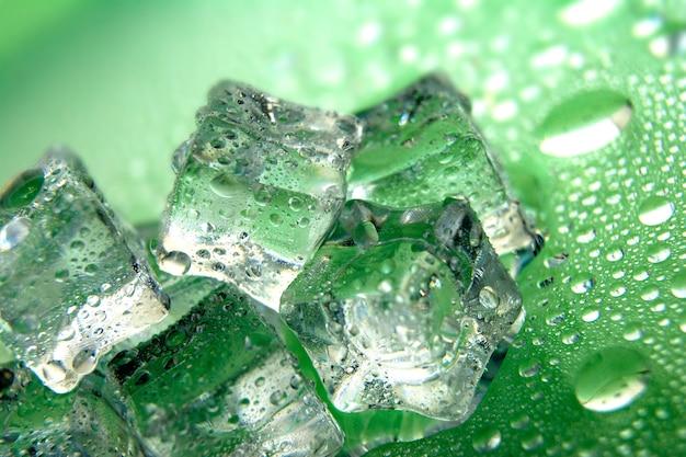Cubetti di ghiaccio di fusione su un colore verde con gocce d'acqua